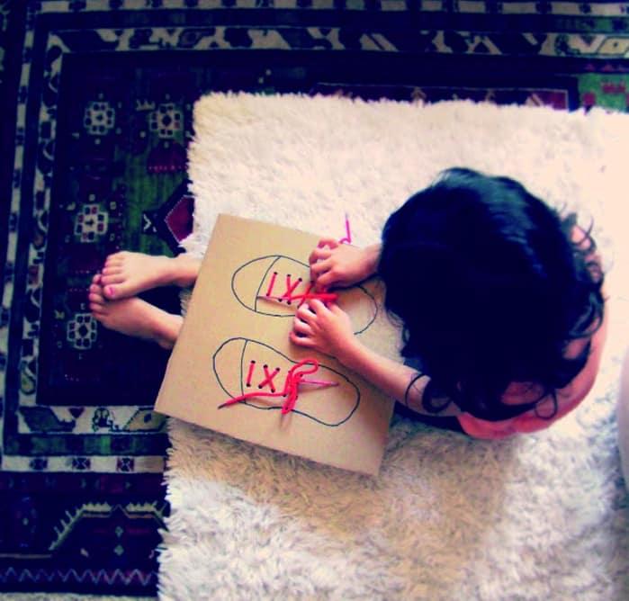 niña aprendiendo a atar cordones